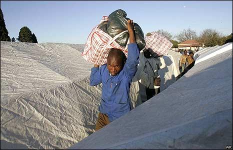 Man carrying belongings between tents