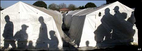 Immigrants stand next to their tents in a informal refugee camp outside a police station in Primrose east of Johannesburg, South Africa, Thursday May 22