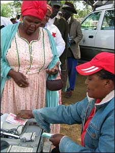 A woman in Otjivero, Namibia, receives her monthly payment