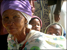 An elderly woman in Otjivero, Namibia, with a child on her back