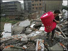 A woman carries bedding across the debris in Sichuan province - 23/05/08