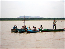 Kids sit in boats and chat on the Tonle Sap