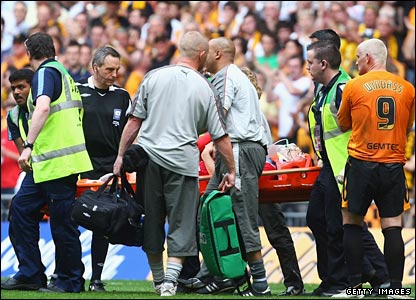 Bradley Orr of Bristol City is stretchered off as Dean Windass of Hull City (R) looks on