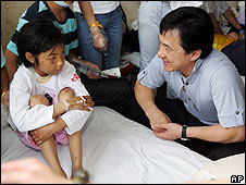 Jackie Chan talks to an injured child as he visits the earthquake victims in hospital