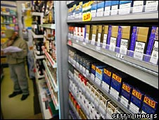 Cigarettes on a shop shelf and a man standing in the background