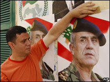 Man puts up a poster of General Michel Suleiman in Beirut