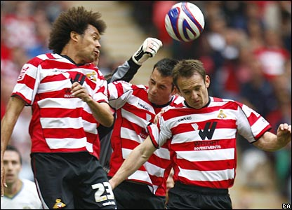Doncaster Rovers' James Hayter (right), Sam Hird (centre) and Jason Price challenge for the ball in the air with United goalkeeper Casper Ankergren