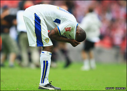 A defeated Tresor Kandol of Leeds pulls his shirt over his head and stands dejected