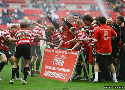 Doncaster Rovers players celebrate victory with flowing champagne