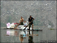 Survivors row a raft across one of the lakes formed by the quake in Majingxiang on 24 May 2008