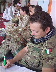 An Italian soldier notes requests for help  from the locals