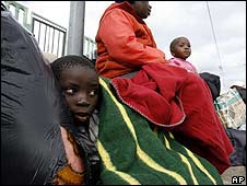 A Mozambican family wait in Primrose, east of Johannesburg, South Africa, for transport to take them home on 26 May