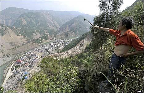 Man points to Tangjiashan lake, next to city of Beichuan