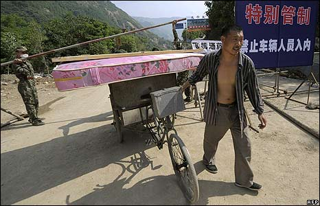 Survivor evacuates with his belongings outside Beichuan town, China