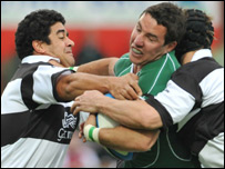 Paddy Wallace (centre) is tackled by Morgan Turinui and Stephen Larkham