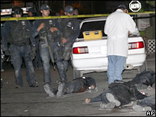 Police officials look on as forensic workers examine the bodies of policemen killed in Culiacan, Mexico, 27 May, 2008