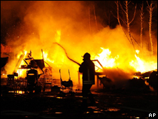 Firemen hose down a camp of Roma people that was set on fire on the outskirts of Naples (file images from 14 May 2008)