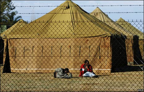 Men rest outside a camp near Pretoria, South Africa, 27 May 2008