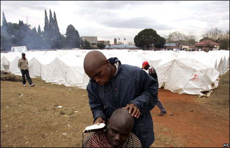 A Mozambican shaves a man's head at a camp in Primrose, near Johannesburg, South Africa, 26 May 2008