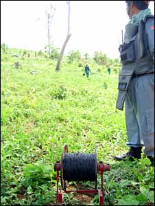 A supervisor waits to detonate a landmine