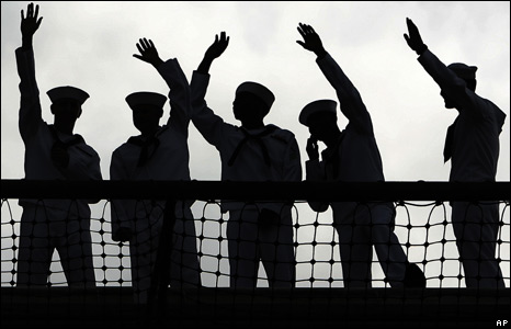 US navy sailors wave farewell as the USS Kitty Hawk leaves Yokosuka Naval Base, Japan