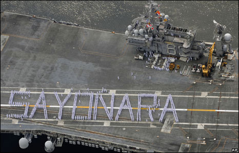 "Crew members aboard the USS Kitty Hawk form the word ""sayonara"" (""goodbye"") as the aircraft carrier leaves Yokosuka"