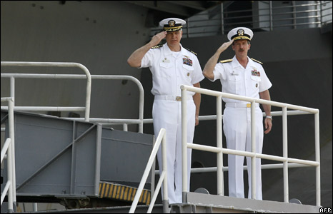 Captain Todd Zecchin (L) and Rear Admiral Richard Wren (R) give a last salute on board the USS Kitty Hawk