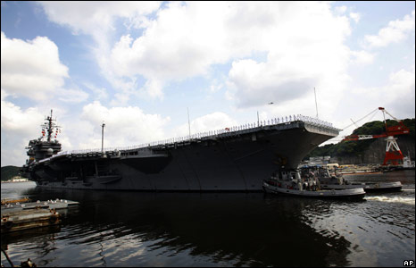 US aircraft carrier USS Kitty Hawk leaves a pier at Yokosuka Naval Base, Japan