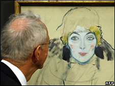 A man examines a Gustav Klimt painting