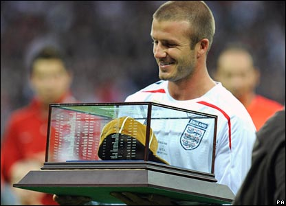 David Beckham is presented with his commemorative 100th cap by Sir Bobby Charlton
