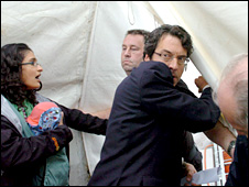 George Monbiot is led away by security officers