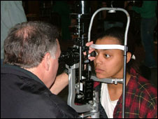 A patient receives an eye examination from an RAM volunteer