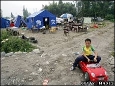 A young boy sits outside a temporary tent shelter in Pengzhou, Sichuan province, on 23 May 2008