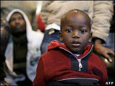 A child takes refuge with his family at a community centre in Cape Town