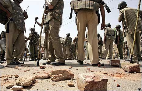 Policemen stand near brickbats used by Gujjars outside of Delhi