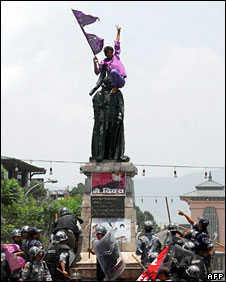 Nepali anti-riot police try to detain a man sitting on top of the statue of former king Mahindra outside the royal palace in Kathmandu, 29 May, 2008