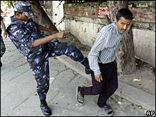 A policeman kicks a man as police disperse demonstrators in Kathmandu, 29 May, 2008