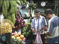 Man buying fruit from market trader