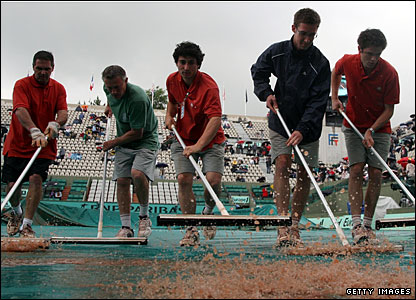 The Roland Garros groundtsaff do their bit and play resumes after 90 minutes