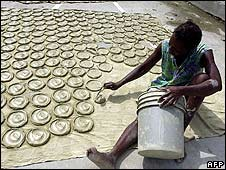 "A Haitian woman bakes ""biscuits"" made out of clay and vegetable oil in the sun in Port-au-Prince on 9 May"