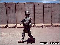 A US soldier patrols near a concrete blast wall east of Baghdad