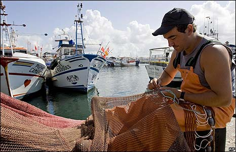 Fishermen mends his nets while striking in Portugal.