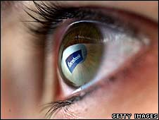 The Facebook logo is reflected in a human eye