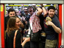 Revellers drink on a Circle line tube train