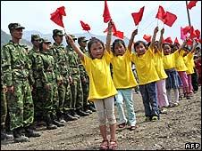Soldiers watching children dance at Leigu refugee camp 1/6/08