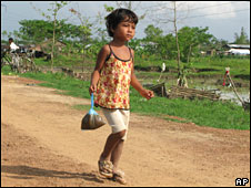 A refugee girl with a food donation from monks near Rangoon on 1 June 2008