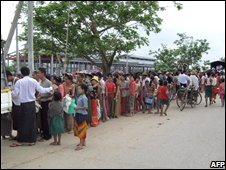 People queue up for food handouts in the town of Tontay