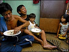 Marlon Dizon eats cheap government subsidised rice for lunch with his relatives in a poor community in Manila, Philippines, in May 2008.