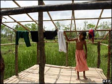 A young girl dries clothes on the damaged roof of her home in Twantay on 29 May 2008