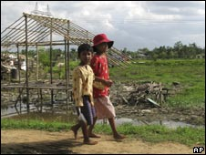 Two Burmese boys walk past a hut destroyed by Cyclone Nargis
